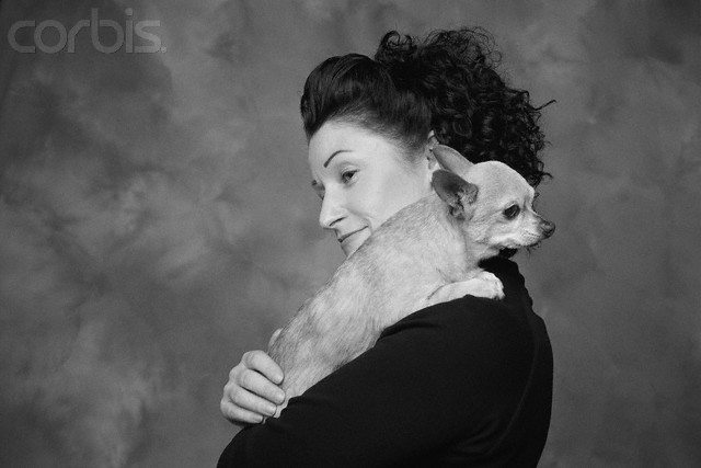 Woman Carrying Dog on Shoulder