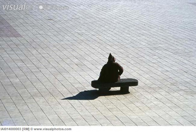 Hooded figure sitting alone on bench