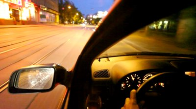 stock-footage-car-driving-on-night-city-street-with-railroad-view-on-wheel-and-mirror